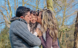 Happy couple kissing her daughter over a forest Stock Images