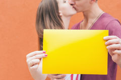 Happy couple kissing and holding frame at red background Stock Image