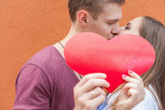 Happy couple kissing and holding a heart at red background Royalty Free Stock Images