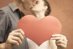 Happy couple kissing and holding heart at red wall background Stock Image