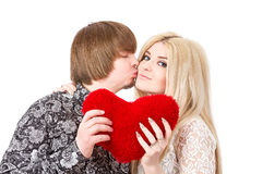 Happy couple kissing and holding red valentine's heart Stock Photos
