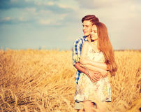 Happy couple kissing and hugging outdoors. On wheat field, love concept Royalty Free Stock Images