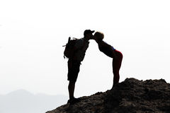 Happy couple kissing on mountain summit royalty free stock photos