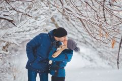 Happy Couple Kissing Outdoors in Snow Park. Winter Vacation.  Stock Photography