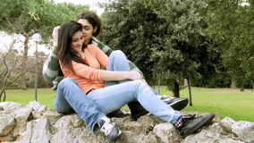 Happy couple kissing in park having fun. Young handsome man kissing girlfriend in park stock video