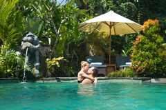 Happy couple kissing while relaxing in outdoor spa infinity swimming pool surrounded with lush tropical greenery of Ubud. Bali. Luxury spa and wellness stock photography
