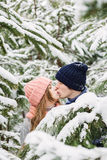 Happy couple kissing among snowy fir trees Royalty Free Stock Images
