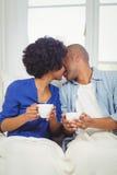 Happy couple kissing on the sofa Royalty Free Stock Photos