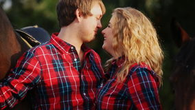 Happy couple kissing on a walk around the horses stock footage