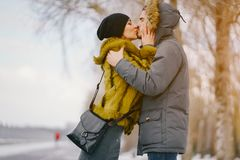 Happy couple walking through the park on a sunny winter day. Happy couple kissing and walking through the park on a sunny winter day Royalty Free Stock Image