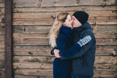Happy couple kissing on a wooden background under snowfall. Happy young loving couple kissing on a wooden background near countryhouse under snowfall Stock Images