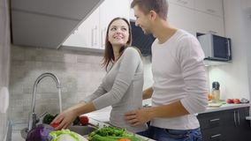 Happy couple on the kitchen cooking together stock video