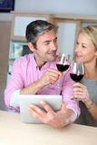 Happy couple in the kitchen drinking wine Stock Photo