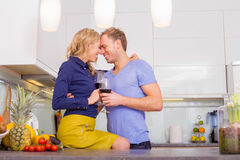 Happy couple in kitchen drinking wine Royalty Free Stock Images