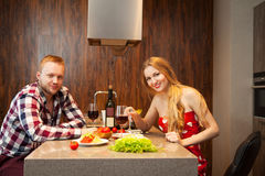 Happy couple in a kitchen eating pasta Stock Images