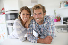 Happy couple in the kitchen. Portrait of couple standing in modern kitchen stock images
