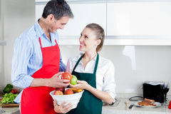 Happy Couple in Kitchen Preparing Food Stock Photos