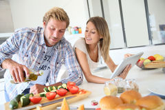 Happy couple in the kitchen preparing meal Stock Image