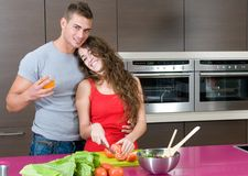 Happy couple in the kitchen with salad Stock Photos