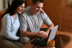 Happy Couple With Laptop 2. Man and woman sitting on the sofa with laptop on the table Stock Photo