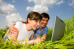 Happy couple on a laptop. Computer outdoors. Lay on the green grass Stock Image