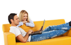 Happy couple with laptop computer. Happy young man and woman sitting together and looking at computer screen Stock Image