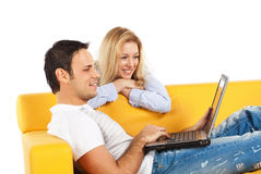 Happy couple with laptop computer. Happy young man and woman sitting together and looking at computer screen stock images