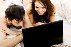 Happy couple on laptop computer in bedroom. Royalty Free Stock Photography