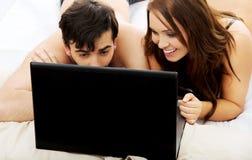 Happy couple on laptop computer in bedroom. Stock Photos