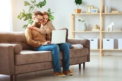 Happy couple with laptop computer at home stock photos