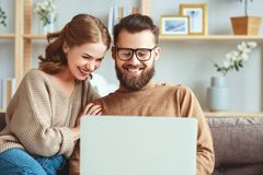 Happy couple with laptop computer at home stock photo