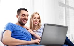 Happy couple with laptop computer at home stock image