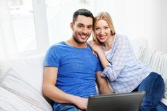 Happy couple with laptop computer at home stock images