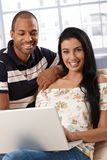 Happy couple with laptop computer smiling Royalty Free Stock Images