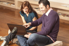 Happy couple with laptop on the floor Stock Images