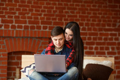 Happy couple with laptop spending time together at home, smiling and having fun Stock Photo