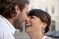 Happy couple laughing. Beautiful female and attractive male kissing and laughing stock images
