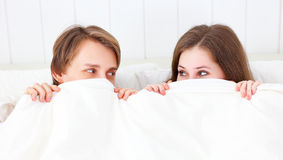 Happy couple laughing in bed peeking out from under blanket Royalty Free Stock Photos