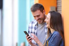 Happy couple laughing checking smart phone royalty free stock images
