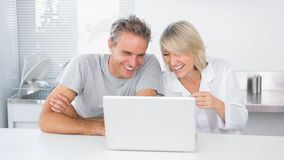 Happy couple laughing at laptop in the morning. Sitting at kitchen counter Stock Photos
