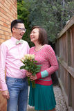 Happy couple laughing / smiling. Happy couple with vibrant colored clothing laughing, smiling. women holding flowers royalty free stock images