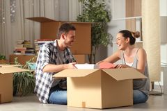 Happy couple laughing unboxing belongings moving house royalty free stock images
