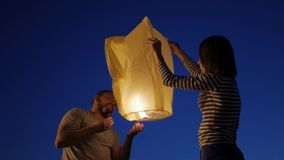 Happy couple launching a Chinese sky fly fire lanterns to make a wish, family. stock footage