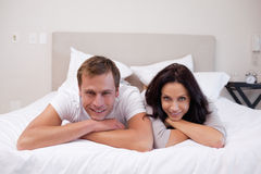 Happy couple laying on the bed together Royalty Free Stock Photos