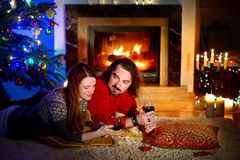 Happy couple laying by a fireplace in on Christmas eve Stock Photo