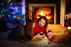 Happy couple laying by a fireplace in on Christmas eve Royalty Free Stock Photos