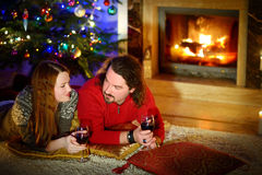 Happy couple laying by a fireplace in on Christmas eve Royalty Free Stock Images