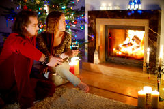 Happy couple laying by a fireplace in on Christmas eve Stock Image