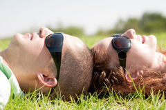 Happy couple laying on a lawn and looks. At the sky Stock Photos