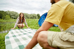 Happy couple laying picnic blanket at campsite Stock Photography